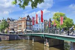 Bro över en kanal i Amsterdam den gamla staden Arkivfoto