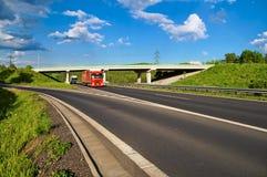 Bro över en tom huvudväg i bygden, under en bro som passerar två lastbilar Arkivfoton