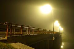 Bro över floden och det virvlade ljuset av gatalampor i tung dimma på natten royaltyfri foto