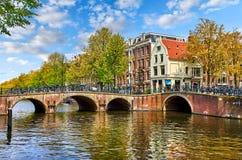 Bro över kanalen i Amstel för Amsterdam landskap för vår för stad för nederländsk husflod gränsmärke gammalt europeiskt Arkivfoton