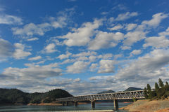 Bro över sjön Shasta under molnig himmel arkivfoton