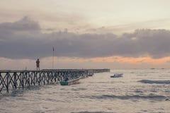 Bro av pir i stranden på solnedgången royaltyfria bilder