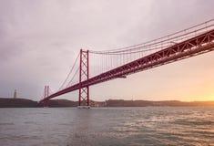 Bro 25 de Abril och Kristus konungmonumentet i Lissabon under solnedgång Royaltyfria Bilder