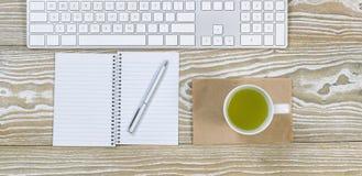 Büro-Desktop mit grüner Tee-Getränk Stockbilder