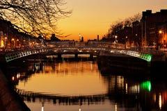 Bro för mummel`-encentmynt och de norr bankerna av floden Liffey i Dublin City Centre på natten Arkivbild