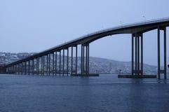 Bro för Tromsoe stadsö under dimma för tungt väder över förkylningblåttfjorden arkivbild