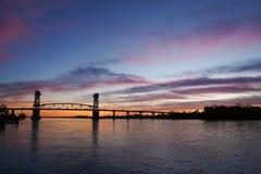 Bro för uddeskräckflod på solnedgången Arkivfoto