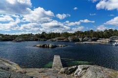 Bro i en liten stenig fjärd på fjorden Royaltyfri Fotografi