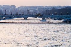 Bro i Paris på rosa färgblåttsolnedgång Royaltyfria Bilder
