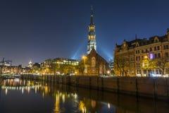 Bro i Speicherstadt i Hamburg nattljus och himmel Kyrklig sikt arkivbilder