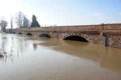 Bro med den fulla floden Floden är full Bro som korsar floden som översvämmar Fotografering för Bildbyråer