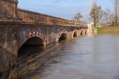 Bro med den fulla floden Floden är full Bro som korsar floden som översvämmar Royaltyfri Foto