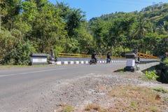 Bro med räcket för gul metall över floden i berg på den Bali ön Statyer för dekorativ sten Folket rider mopeder royaltyfria bilder