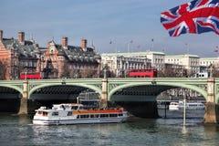 Bro med röda bussar mot stadskryssningskeppet i London, England, UK royaltyfri foto
