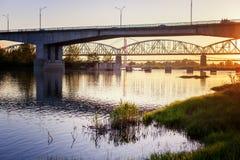 Bro och flod i strålarna av inställningssolen, härlig stad arkivbilder