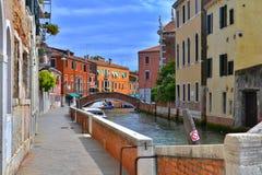 Bro och kulöra hus på sidorna av en liten kanal i Venedig arkivfoto