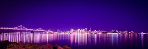 Bro och stad av lampor på natten & reflexionen Arkivbilder