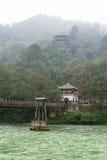 Bro och tempel i ogenomskinligheten i det Dujiangyan berget Arkivfoton