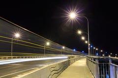 Bro på natten, med ljusa slingor som gör strimmig över den royaltyfria bilder