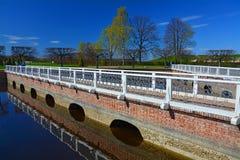 Bro på sektoriella damm i Peterhof, St Petersburg, Ryssland Royaltyfri Bild