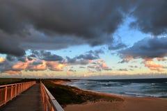 Bro som förbiser en strand på solnedgången Arkivfoton