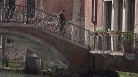 Bro som spänner över en liten kanal i den Venedig och folkkorsningen arkivfilmer