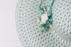 A broad-brimmed female hat is light green, with a buttonhole. Artificial flowers in the form of roses. Stock Photos