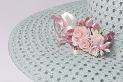 A broad-brimmed female hat is light green, with a buttonhole. Artificial flowers in the form of roses. Stock Images