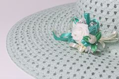 A broad-brimmed female hat is light green, with a buttonhole. Artificial flowers in the form of roses. Stock Photography