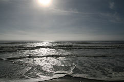 Broad leaden waves in the sea. Sun and clouds under the sandy seashore and leaden wide waves Stock Images