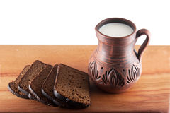 Broad and pitcher of milk on wooden table Royalty Free Stock Photography