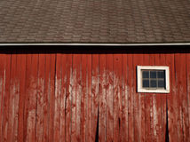 The broad side of a barn. Straight on shot of the side of a red barn with brown shingles and white trim.  A white window is on the right and some of the barn Stock Photos