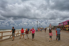 Broad walk in Jersey Shore. Morning before storm. Broad walk in the beach of Jersey Shore. Morning before storm. dramatic cloudy sky. people walk on the wooden Royalty Free Stock Photography