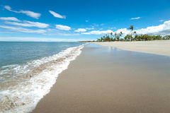 Broad White Sandy Tropical beach. WS: A wide white sandy beach to the blue sea under a blue sky. Small waves rollover the sand Stock Photo