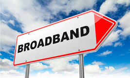 Broadband on Red Road Sign. Broadband - Inscription on Red Road Sign on Sky Background stock photography