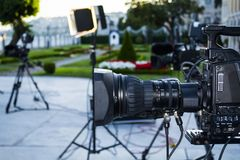 Broadcast tv; movie shooting camera or video production and film, tv crew team with camera. Light and audio equipment at outdoor location stock photo