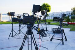 Broadcast tv; movie shooting or video production and film, tv crew team with camera. Light and audio equipment at outdoor location Stock Photos
