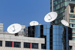 Broadcasting. The view of the whit dish antenas on the roof of the building on the blue sky background Stock Photo