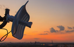Broadcasting antenna in the form of a plate against the background of a beautiful sunset over the city Stock Photo