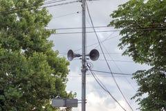 Broadcasting loudspeakers on street. Broadcasting loudspeakers on a e in the city between the trees royalty free stock photo