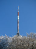 Broadcasting transmitter. Scenic view of broadcasting transmitter tower against blue sky with Wintry trees in foreground Stock Image