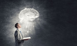 Broaden your mind. Shocked businessman holding opened book with brain picture Royalty Free Stock Images