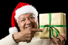 Broadly Grinning Aged Male Pointing At Golden Gift Royalty Free Stock Image
