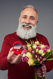 Broadly smiling mature man holding gift box with weddin. Close-up shot of broadly smiling mature man who is holding a gift box with wedding ring and a bunch of Stock Images