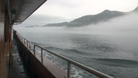 Broadside boat in fog on water of Pacific Ocean on background mountains Alaska. stock footage