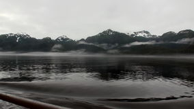 Broadside boat in fog on water of Pacific Ocean on background mountains Alaska. Amazing landscapes. Beautiful rest and tourism in a cool climate. Unique stock footage
