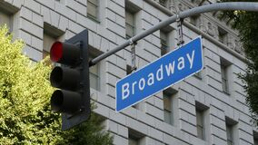 Broadway street name, odonym sign and traffic light on pillar in USA. Road intersection in downtown of city. Crossroad