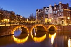 Broar över kanaler i Amsterdam på natten Arkivfoto