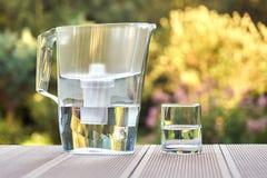 Broc de filtre d'eau et un verre propre d'une fin claire de l'eau sur le fond de jardin d'?t? photo libre de droits