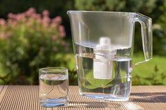 Broc de filtre d'eau et un verre propre d'une fin claire de l'eau sur le fond de jardin d'?t? image libre de droits